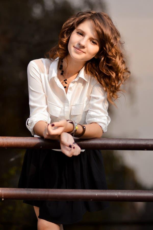 Очень милая тощая, приятная дружелюбная девушка с сияющими, лоснистыми, здоровыми, курчавыми, волнистыми волосами, светлой сторон стоковая фотография rf