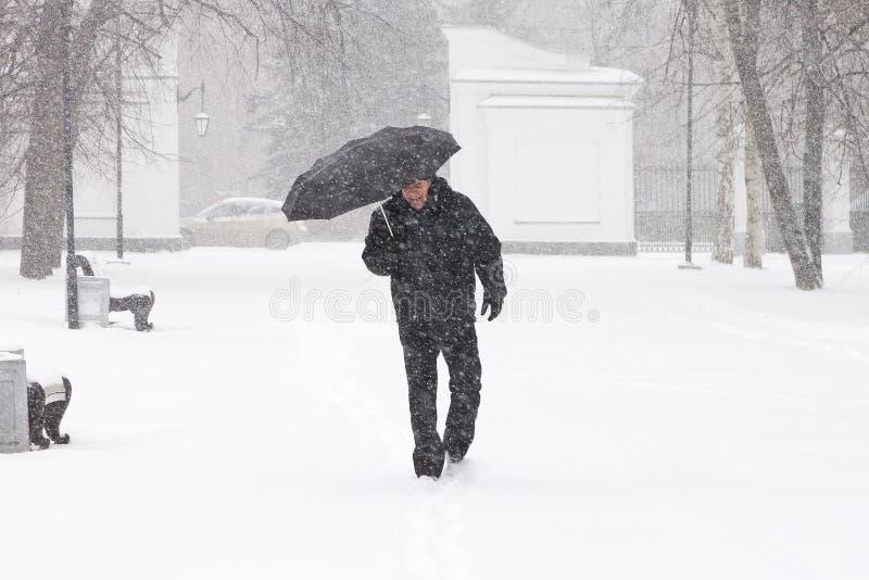 Очень плохая погода в городе в зиме: ужасные сильный снегопад и вьюга Мужской пешеходный прятать от снега под зонтиком стоковое фото rf