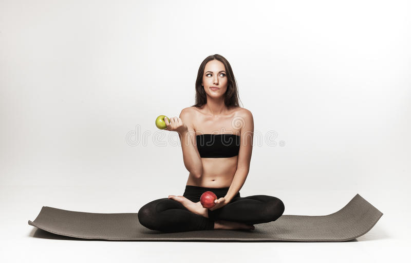 Очень привлекательная молодая женщина сидя на циновке йоги стоковое изображение