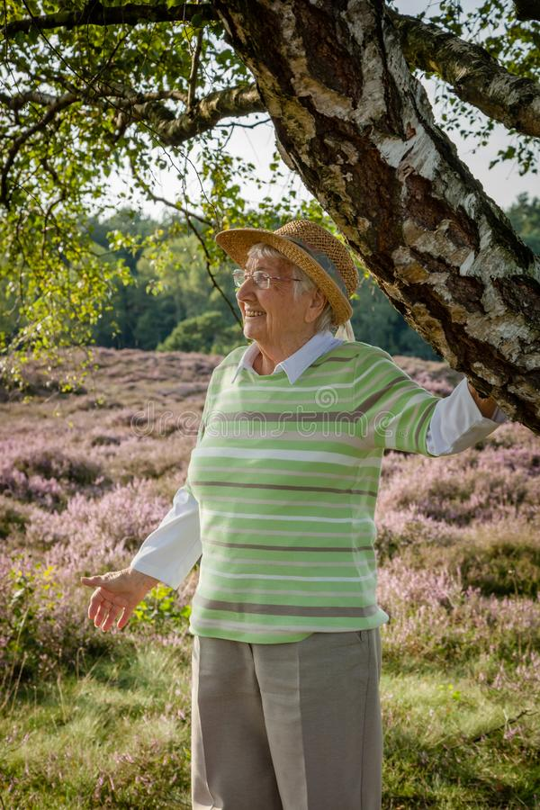 Очень старая счастливая старшая женщина outdoors в вереске причаливает, концепция получая старое счастливое здоровое стоковое изображение