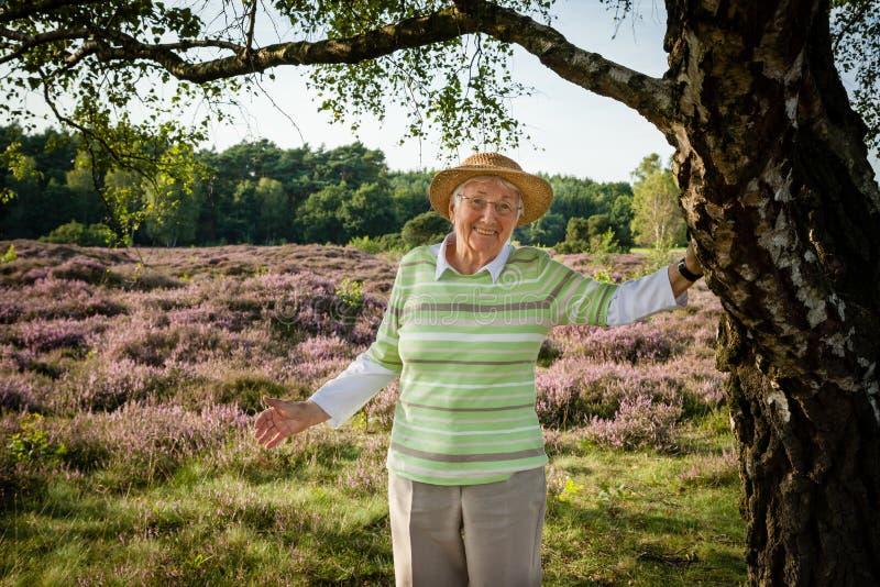 Очень старая счастливая старшая женщина outdoors в вереске причаливает, концепция получая старое счастливое здоровое стоковые фото