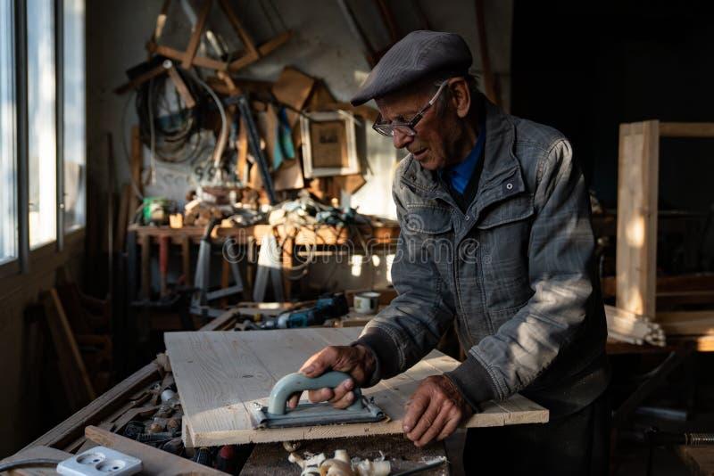 очень старый мастер плотник в очках полирует дерево в домашней мастерской, работая усердно стоковая фотография