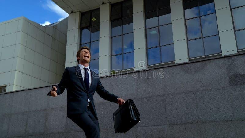 Очень счастливый работник офиса получая продвижение, танцуя outdoors около центра офиса стоковая фотография rf