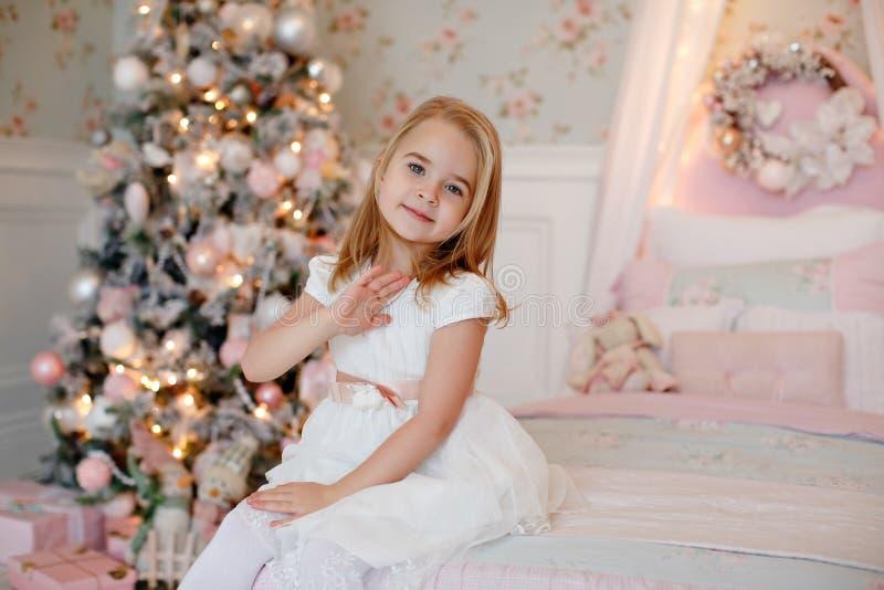 Очень славная очаровательная блондинка маленькой девочки в белом платье сидя дальше стоковая фотография rf