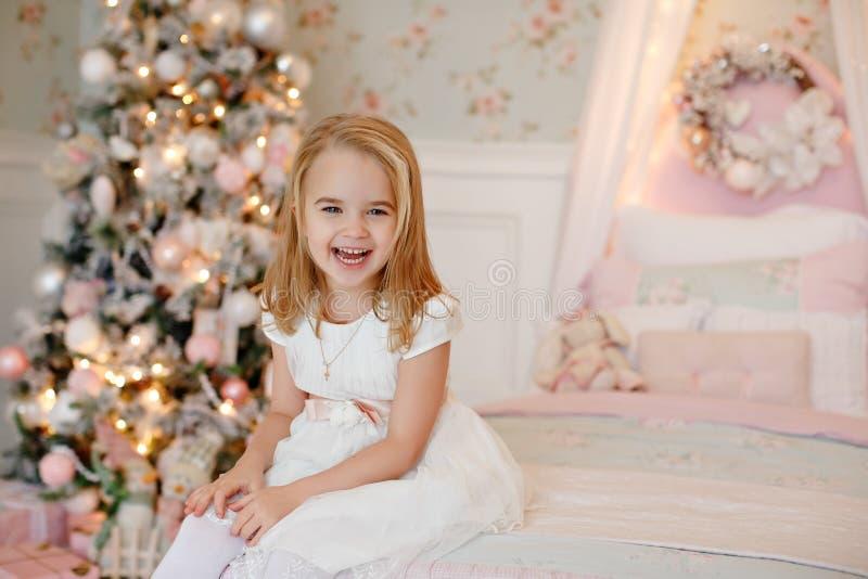 Очень славная очаровательная блондинка маленькой девочки в белом платье сидя дальше стоковые изображения rf