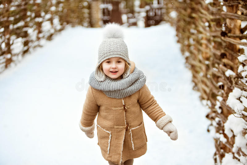 Очень славный красивый ребенок девушки в бежевом пальто и серая шляпа идут стоковые изображения rf