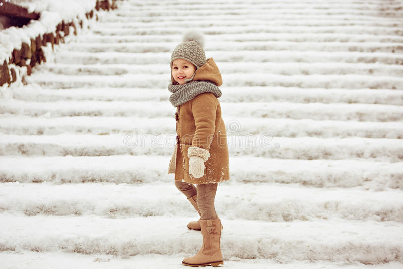 Очень славный красивый ребенок девушки в бежевом пальто и серая шляпа идут стоковая фотография rf