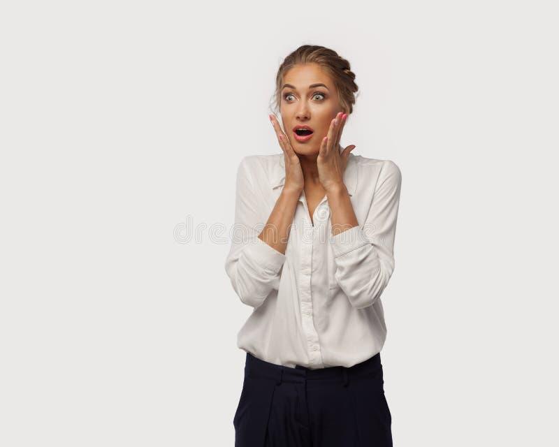 Очень удивленная дама дела одела в классическом офисе одевает принесла ей руки к ее стороне Сюрприз от продаж стоковое фото rf
