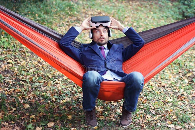 Очень удивленный бизнесмен после использования стекел vr Он отдыхая внутри стоковое фото rf
