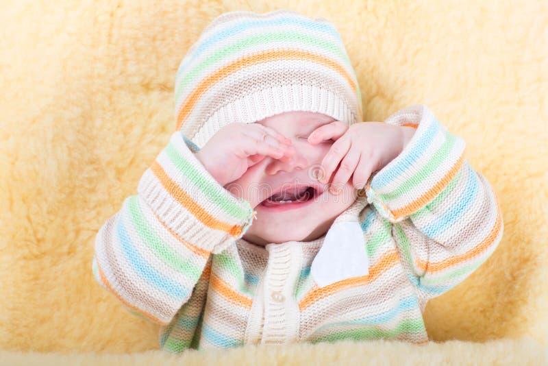 Очень утомленный сонный младенец сидя в теплой овчине стоковая фотография rf