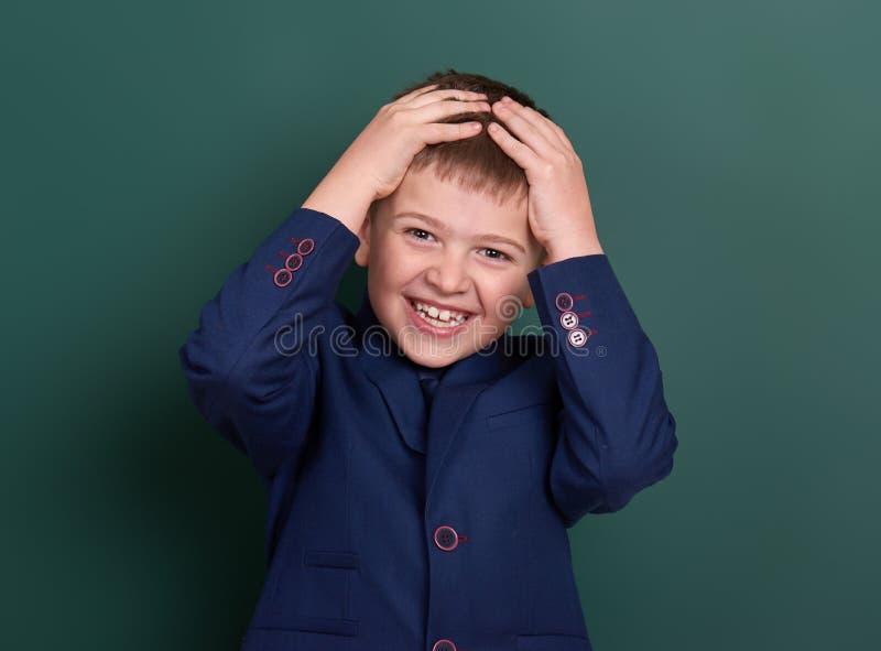 Очень эмоциональный портрет школьника около зеленой пустой предпосылки доски, одетой в классическом черном костюме, один зрачок,  стоковое фото rf