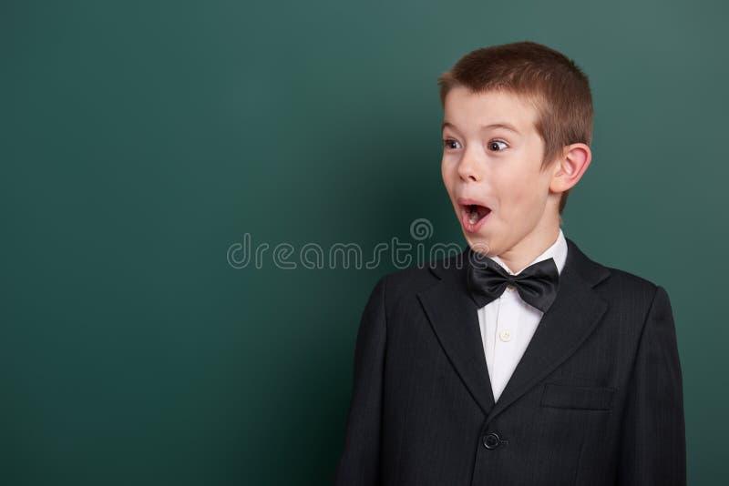 Очень эмоциональный портрет школьника около зеленой пустой предпосылки доски, одетой в классическом черном костюме, один зрачок,  стоковые фото