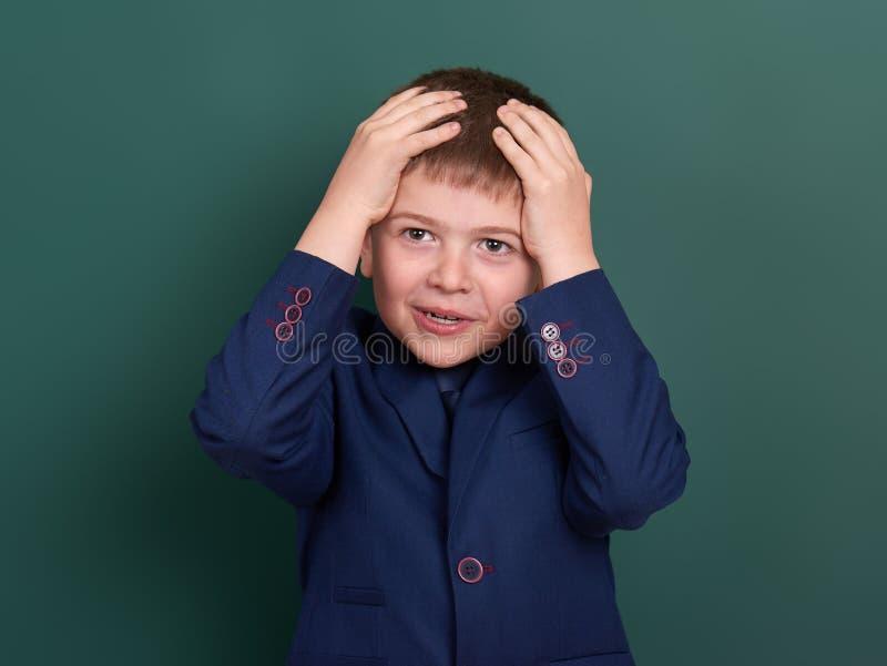 Очень эмоциональный портрет школьника около зеленой пустой предпосылки доски, одетой в классическом черном костюме, один зрачок,  стоковое изображение