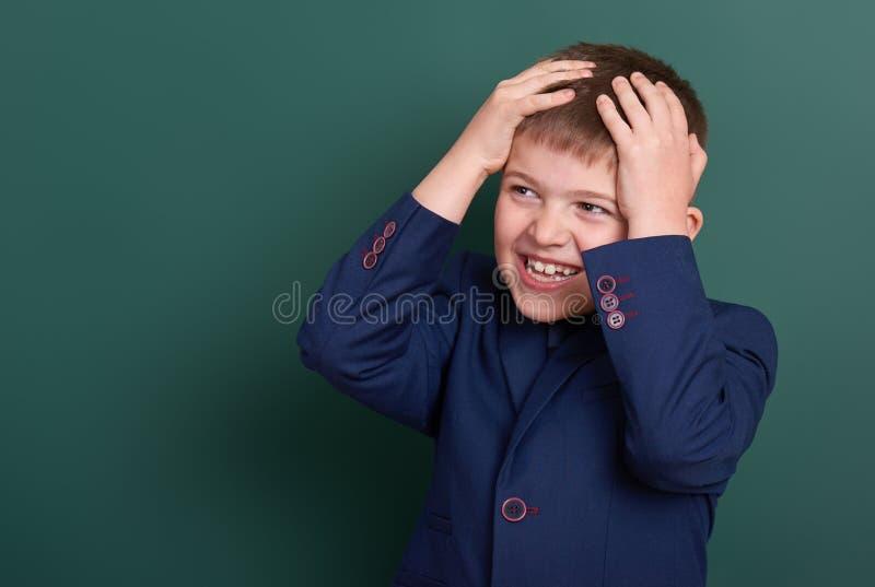 Очень эмоциональный портрет школьника около зеленой пустой предпосылки доски, одетой в классическом черном костюме, один зрачок,  стоковая фотография rf