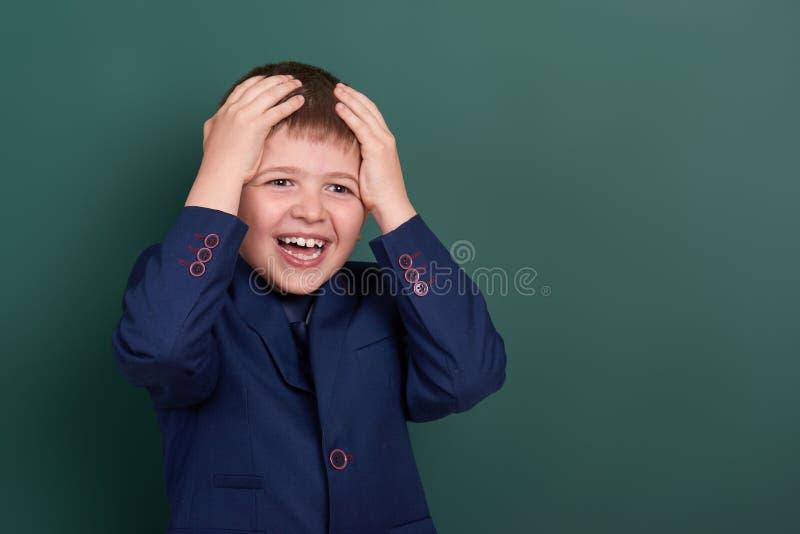 Очень эмоциональный портрет школьника около зеленой пустой предпосылки доски, одетой в классическом черном костюме, один зрачок,  стоковое изображение rf