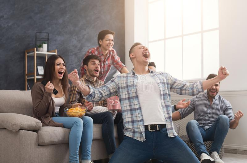 Очень excited друзья наблюдая футбольный матч дома стоковые фото