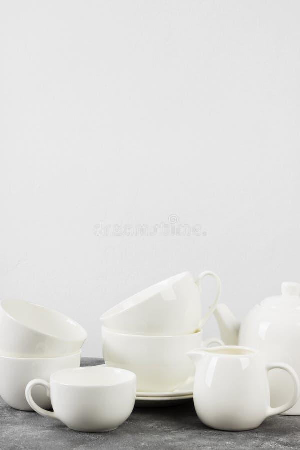 Очистите белый чайник tableware, чашки, поддонники на сером backgrou стоковые изображения