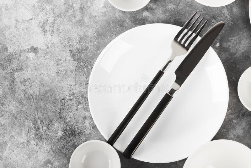 Очистите белый tableware на серой предпосылке Взгляд сверху, космос экземпляра стоковое фото rf