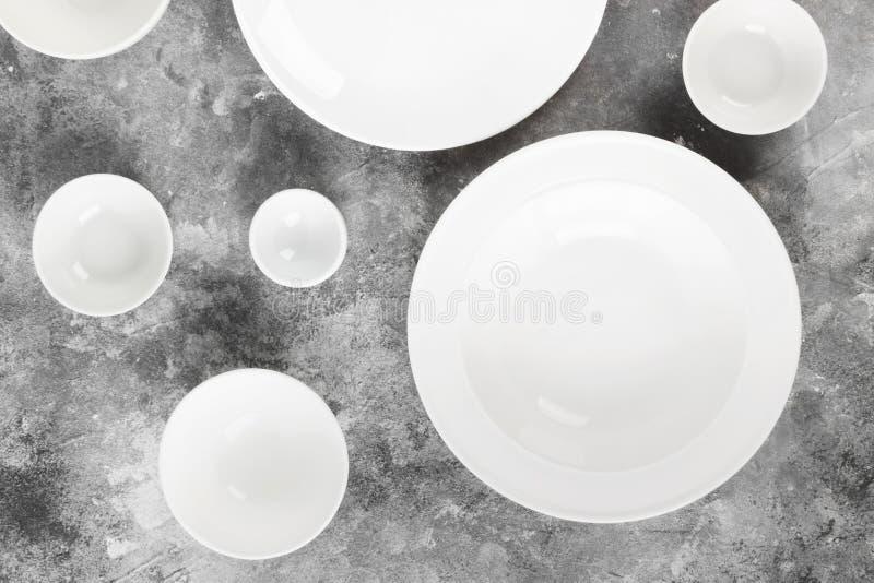 Очистите белый tableware на серой предпосылке Взгляд сверху стоковое изображение