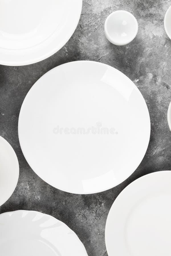 Очистите белый tableware на серой предпосылке Взгляд сверху стоковые фото