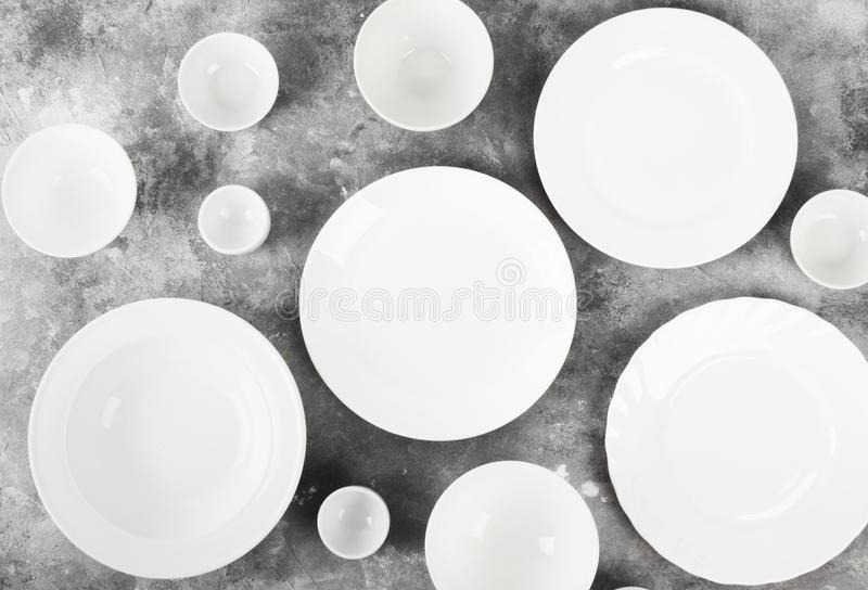 Очистите белый tableware на серой предпосылке Взгляд сверху стоковые изображения