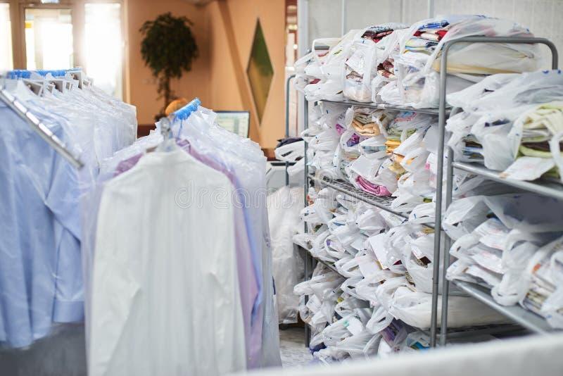 Очистите одежду упакованную в полиэтиленовых пакетах на полках и весьте на вешалках стоковое фото rf