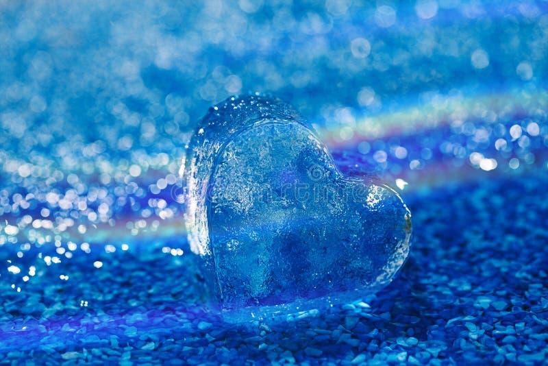 Очистите стеклянное сердце на голубом пляже с водой стоковое фото
