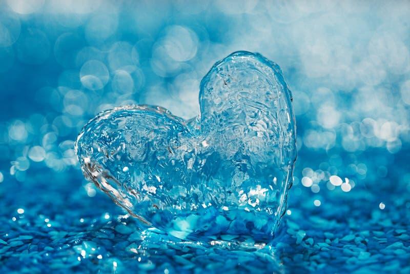 Очистите стеклянное сердце на голубом пляже с капельками воды стоковые фото