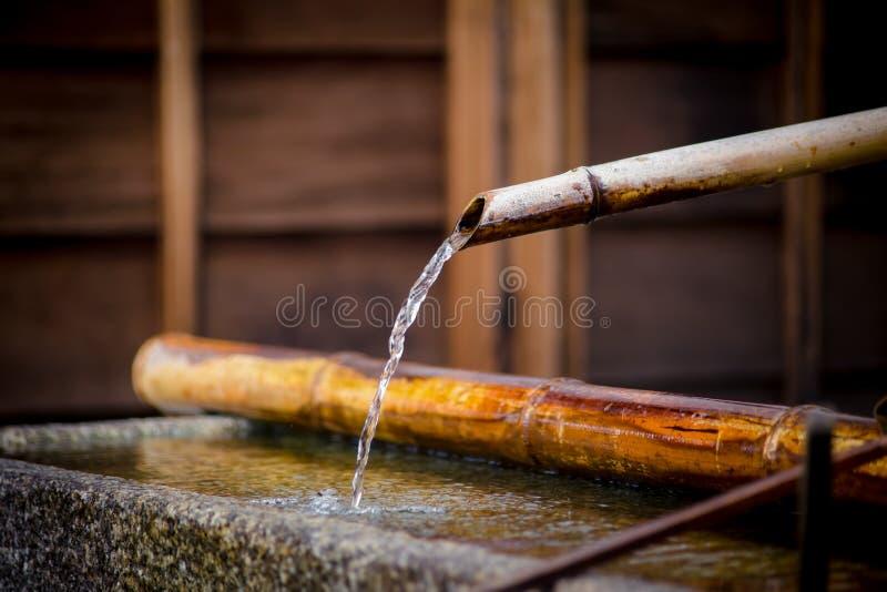 Очистите Rinse воды природы с бамбуковой трубой в каменном ушате на японском виске стоковые изображения rf