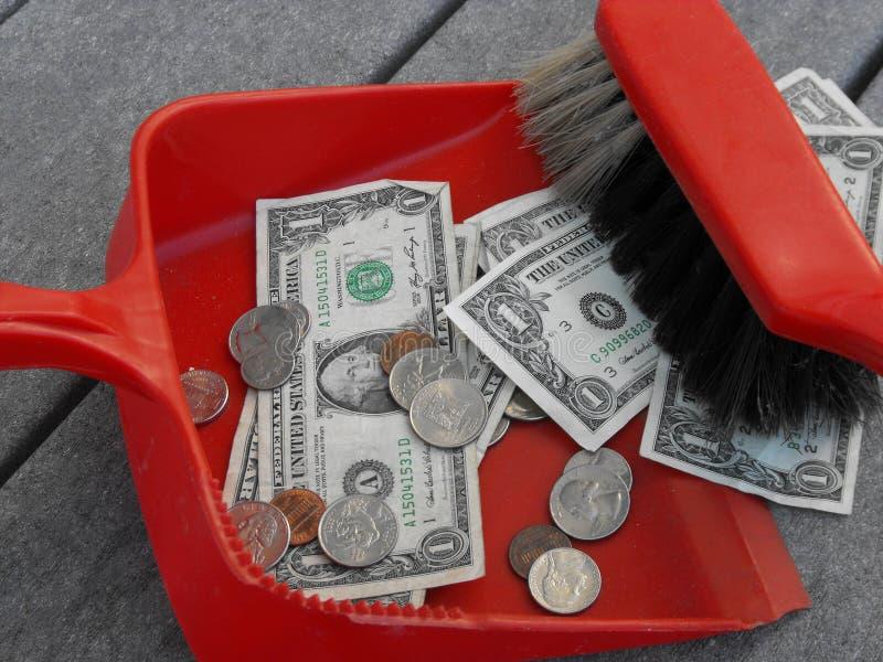 Очищать вверх и широкие поднимающие вверх деньги с dustpan и веником стоковое фото