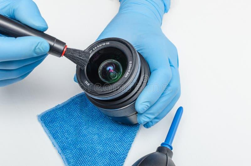 Очищать объектив цифровой фотокамеры и передней линзы загрязнения с щеткой Обслуживание цифровых фотокамер стоковое фото