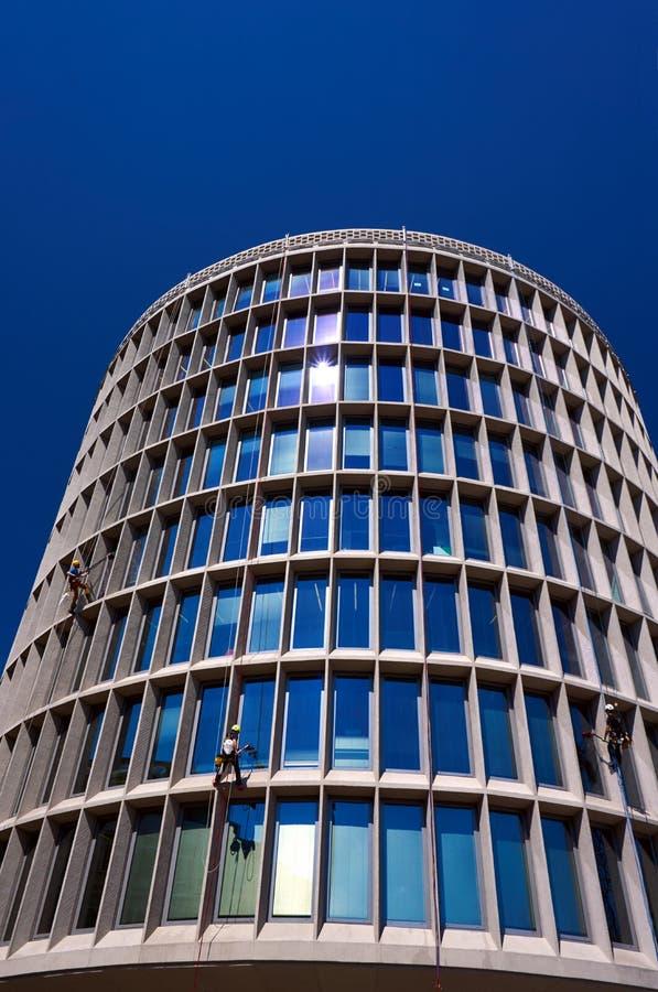 Очищать стеклянные окна на фасаде modernist, круглое здание стоковое изображение