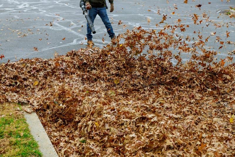 Очищать территории от листьев в людях осени с вениками стоковое фото