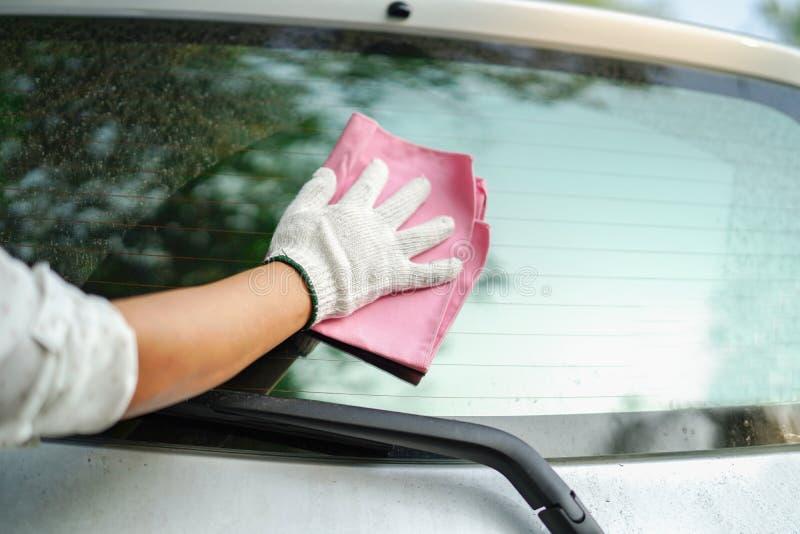 Очищая автомобиль стекла заднего стекла пыли грязный с розовой тканью microfiber стоковое изображение rf