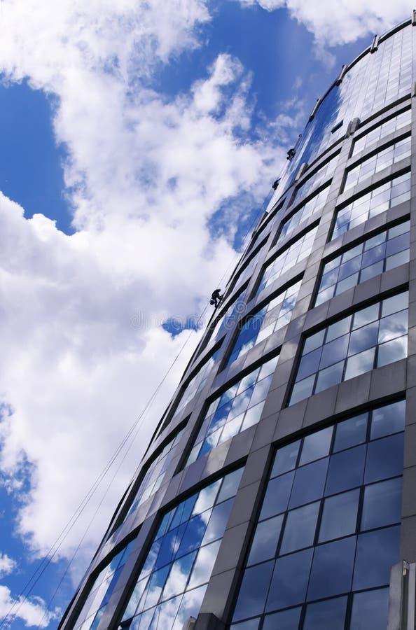 очищая отраженные работники окон небоскреба стоковое фото rf