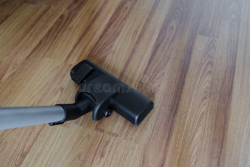 Очищая слоистые деревянные пол, пыль чистки пылесоса и нечистота стоковое фото