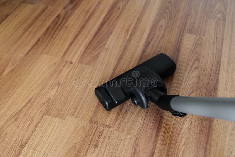 Очищая слоистые деревянные пол, пыль чистки пылесоса и нечистота стоковые изображения