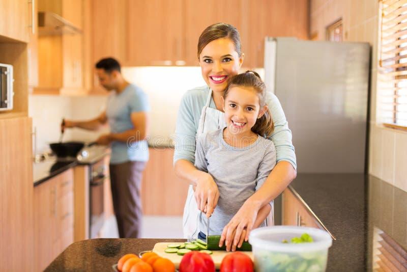 дочь матери подготавливая овощи стоковое изображение rf