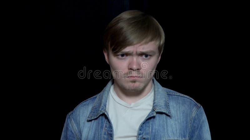 Ощупывание молодого человека унылое Милый человек грустный с нарушенным выражением Человеческие выражения лица и эмоции Изолирова стоковое изображение