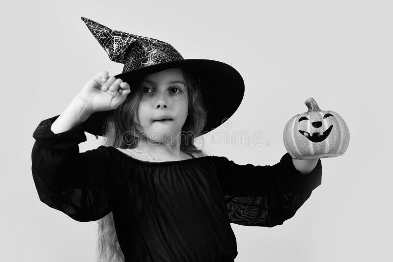 Оягнитесь в черной шляпе ведьмы, платье и смешной стороне Девушка при высекаенная оранжевая тыква изолированная на теплой желтой  стоковые фотографии rf