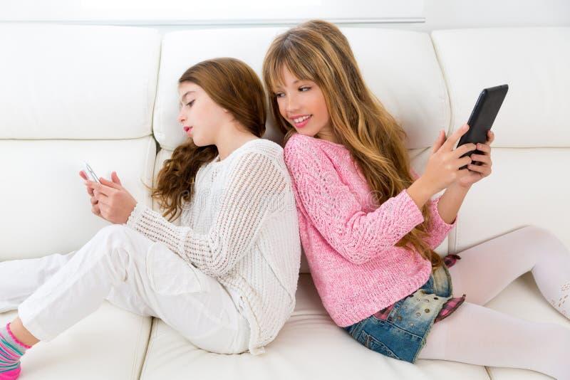 Оягнитесь девушки имея потеху играя спина к спине с ПК таблетки на софе стоковое фото rf
