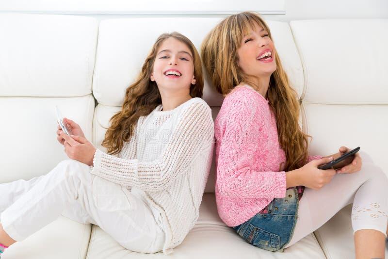 Оягнитесь девушки имея потеху играя спина к спине с ПК таблетки на софе стоковые изображения