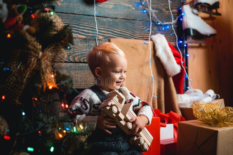 Оягнитесь иметь потеху около рождественской елки внутри помещения hildren подарок Дети рождества Украшение рождественской елки Де стоковые изображения