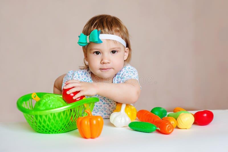 Оягнитесь иметь таблицу вполне пластичной еды Жизнерадостный малыш есть здоровые салат и плодоовощи стоковое фото rf