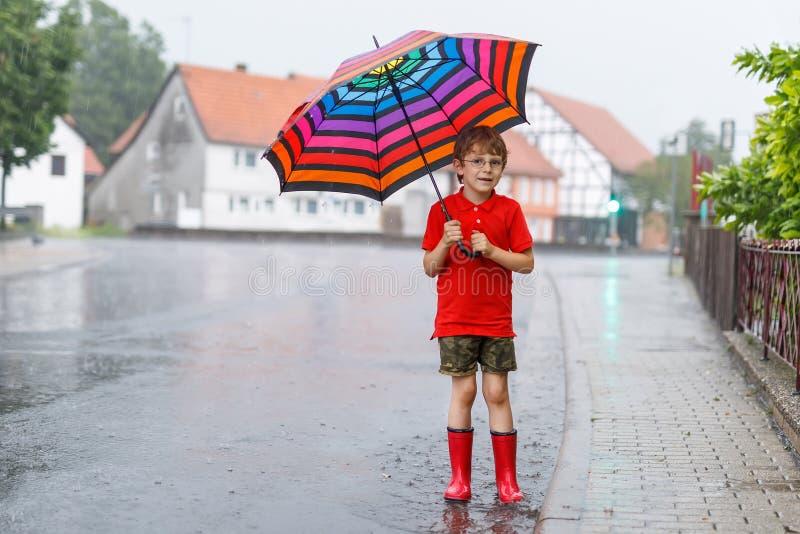 Оягнитесь мальчик нося красные ботинки дождя и идя с красочным зонтиком на улице города Ребенок с стеклами на летний день стоковые фотографии rf