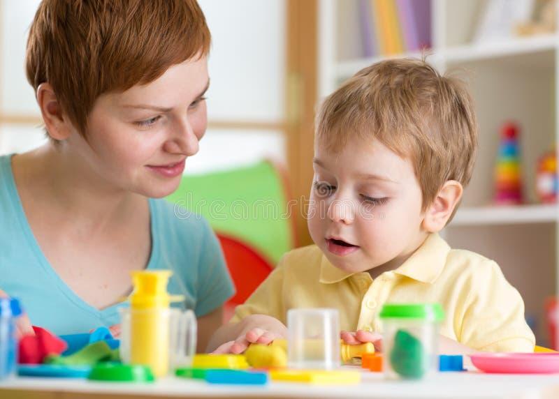 Оягнитесь мальчик с глиной игры учителя дома, детским садом, детским садом или playschool стоковые изображения rf