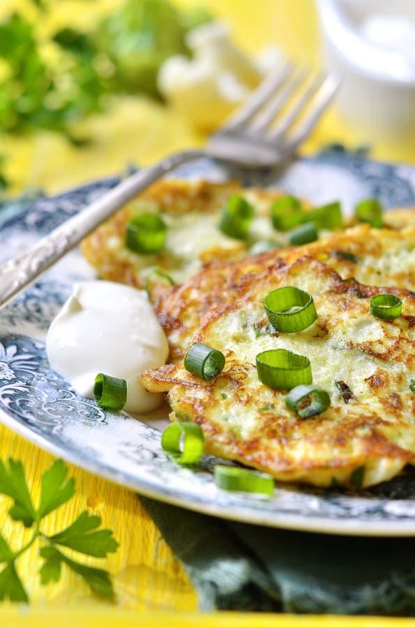 Оладь оладьи цветной капусты и брокколи с сыром стоковые фото