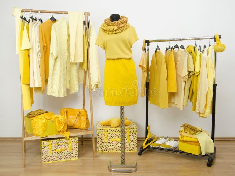 Одевать шкаф с желтыми одеждами аранжировал на вешалках и wi стоковое изображение rf
