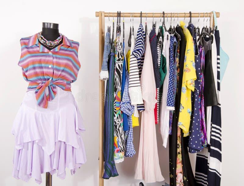 Одевать шкаф с красочными одеждами аранжировал на вешалках и a стоковые фотографии rf