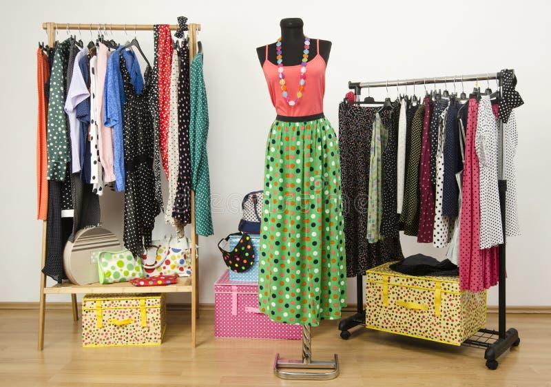Одевать шкаф с одеждами точек польки аранжировал на вешалках. стоковая фотография